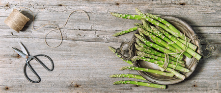 Asparagus vegetables with vintage scissors on rustic wooden background Stock Photo