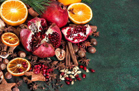 Fruits pomegranate and orange with spices and ingredients for mulled wine cinnamon, star anise, cardamon