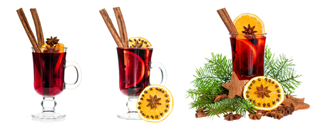 Mulled wine with slice of orange, cinnamon sticks, anise and Christmas tree decoration isolated on white background