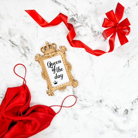 Red dress, golden frame, gift box. Minimal flat lay. Fashion blog concept