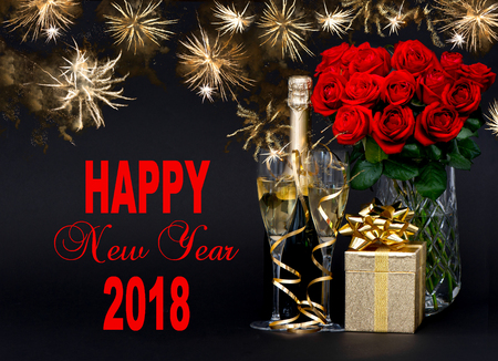 Happy New Year 2018! Greetings card concept. Red roses, bottle champagne, golden gift. Golden fireworks on black background