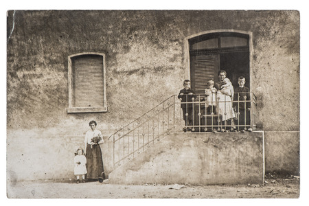 Antique photo of a family with children and house on background