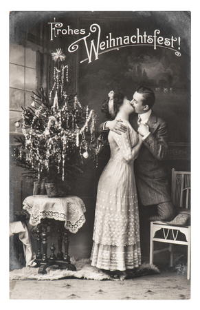 BERLIN, GERMANY - CIRCA 1911: rare antique german postcard showing young couple celebrated with christmas tree. Vintage picture from ca. 1911, in Berlin, Germany