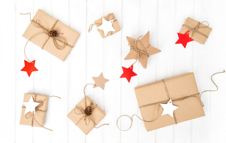 Wrapped gift boxes with decoration on bright wooden background. Holidays flat lay Stock Photo