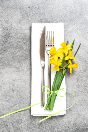 Fork, knife and napkin over table background with spring daffodils flowers decoration