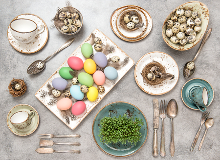 Easter decoration with colorful eggs and birds feather. Holidays table setting background