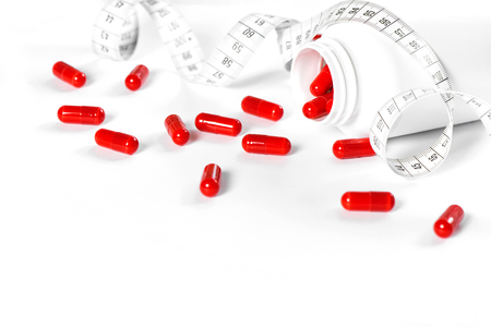 Weight loss pills and measuring tape on white background. Diet, health and detox