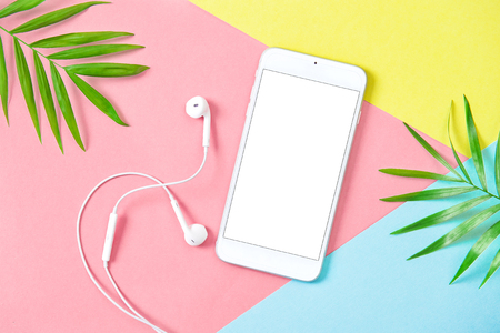 Mobile phone with headphones on summer holidays flat lay background