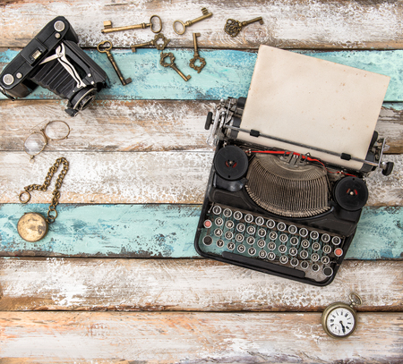 Antique typewriter and vintage accessories on wooden background. Flat lay still life Banco de Imagens
