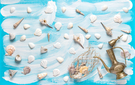 Nautical background with fishing net, sea shells, golden vessel on turquoise blue painted wooden board. Maritime flat lay Stock Photo