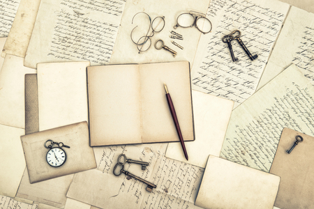 Old letters and postcards, open journal, vintage accessories. Used paper background Archivio Fotografico