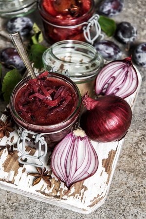 Red onion confiture in jar. Vegetable jam. Plum marmalade. Preserving ingredients Stock Photo