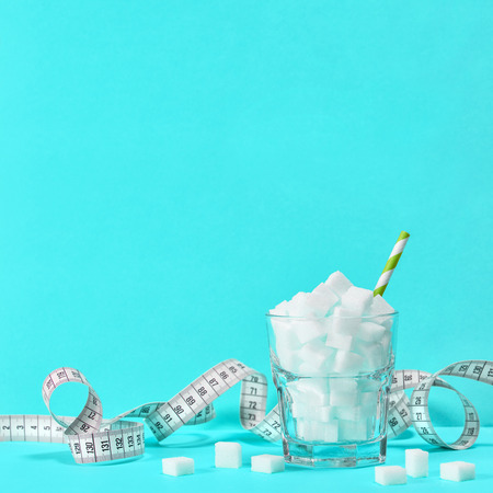Glass with sugar cubes and measuring tape. Weight control, diet and detox concept blue background