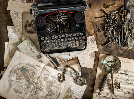 Antique typewriter and vintage office accessories on wooden table. Nostalgic still life