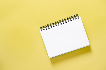Spiral book on yellow background. Paper notebook