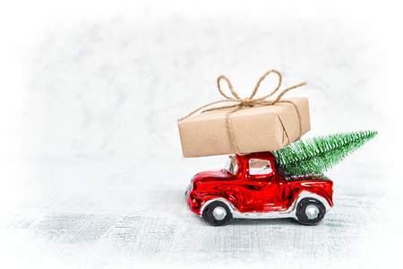 Red car with gift box and Christmas tree on white background Stock Photo