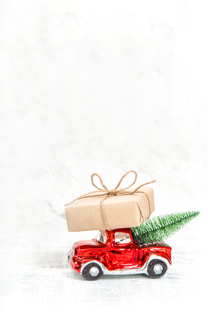 Red car with gift box and Christmas tree. Winter holidays decoration