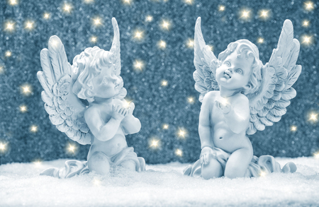 Little guardian angels in snow with golden lights. Christmas decoration