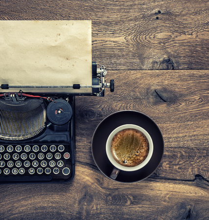 Vintage typewriter with grungy paper page and black coffee. Retro toned