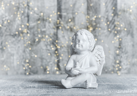 Little guardian angel with festive lights background. Christmas decoration Stockfoto