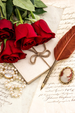Old letters, red rose flowers and antique feather pen. Valentined Day Love concept
