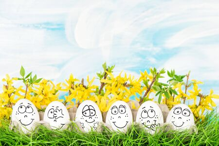 Easter eggs with yellow flowers decoration in green grass Stock Photo