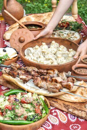 Georgian food. Caucasian shashlik, khinkali, salad. Dinner table on nature background