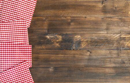 Hölzerner Küchentischhintergrund und karierte Tischdecke