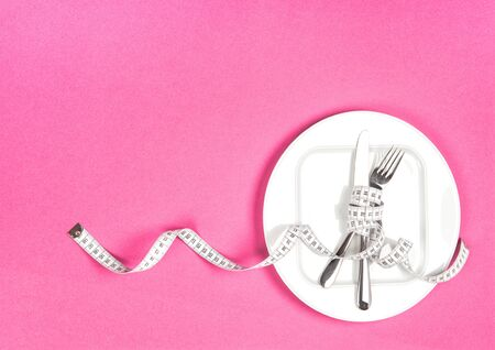Measuring tape and white plate on pink background. Diet, health, weight controll, detox. Flat lay