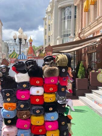 Moscow, Russia - JULY 05, 2019: russian winter fur hats with army emblems on the Old Arbat street gift shop, popular souvenir from Russia