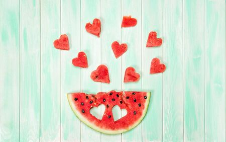 Watermelon hearts on wooden background. Creative summer food concept