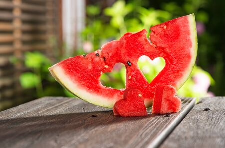 Watermelon hearts on nature outdoors background. Food concept