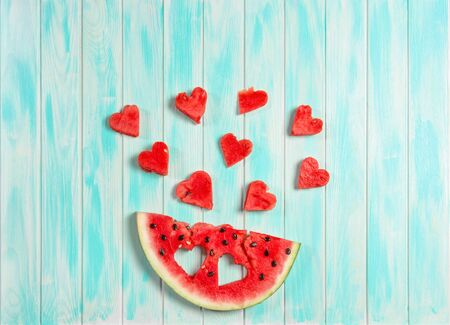 Watermelon hearts on blue wooden background. Fruits berries
