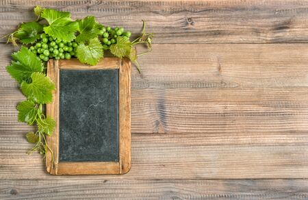 Chalkboard with grapes and green vine leaves decoration on wooden background Stock fotó