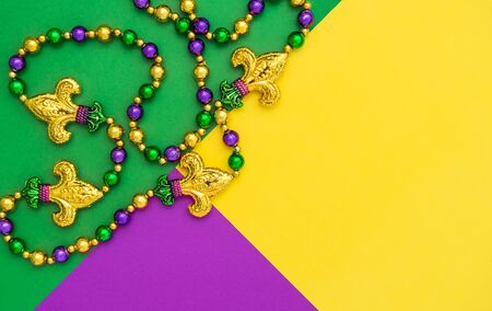 Mardi gras carnival decoration beads on yellow green purple background