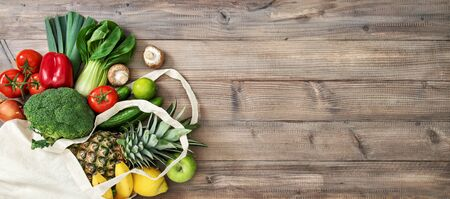 Fresh fruits vegetables in cotoon bag. Tomato, cucumber, broccoli, pineapple, apple, banane, salad. Healthy food