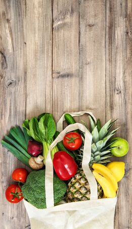 Vegetables and fruits in cotoon bag. Tomato, cucumber, broccoli, pineapple, apple, banane, salad