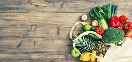 Fresh fruits vegetables in cotton bag. Healthy food. Vintage toned picture Standard-Bild