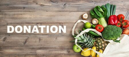 Food donation. Healthy nutrition fruits vegetables in cotoon bag on wooden background