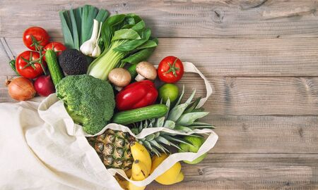 Fresh vegetables fruits in cotoon bag. Tomato, cucumber, broccoli, pineapple, avocado, banane, salad. Healthy food