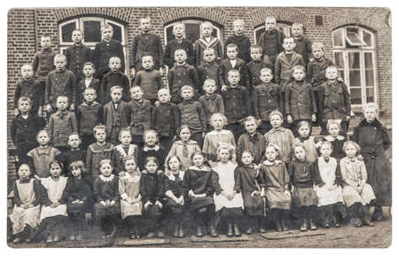 Old photo of school classmates. Group of children and teacher outdoors. Vintage picture with original film grain and blur