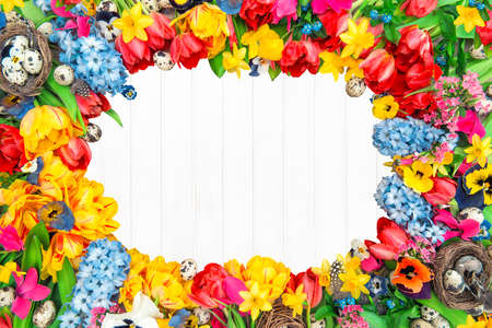 Holidays background from spring flowers and easter eggs. Tulips, narcissus, hyacinth and pansy blossoms