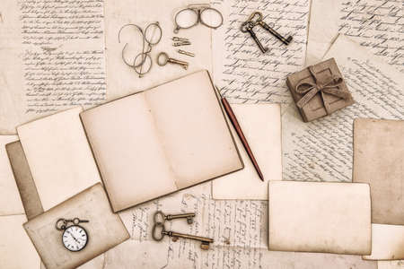 Open book and old handwritten letters. Vintage style flat lay background