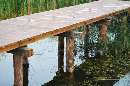Wooden bridge over the pond close-up. Reeds and reflection in the water. 写真素材