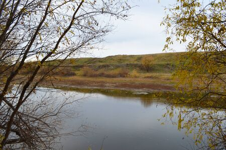 River, trees. Hilly terrain. Autumn nature, fallen leaves and rainy sky. Banco de Imagens