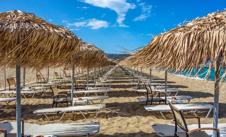 Rows of umbrellas and sunbeds on empty beach. Greece. Crete Stock Photo