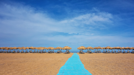 Umbrellas and sunbeds on sunny empty beach. Greece. Crete Stock Photo