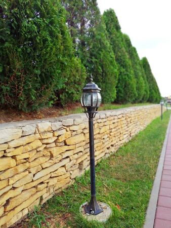 alley with lanterns. Tui and stone fence in the park