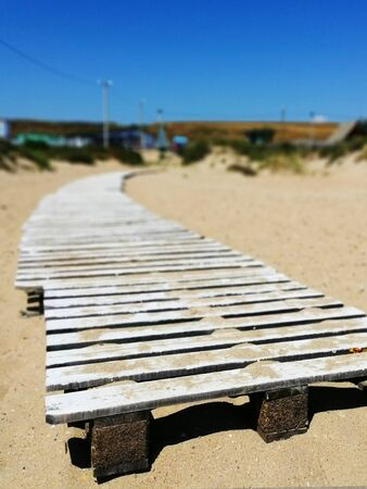 white metal fence, goes into the distance, in perspective, in the sand and against a blue cloudless sky