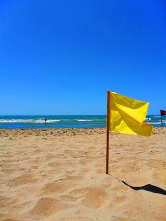 yellow flag by the sea on a sandy beach Banco de Imagens